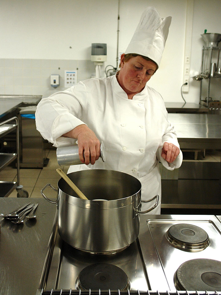 chef working in a commercial kitchen with stainless steel work surfaces